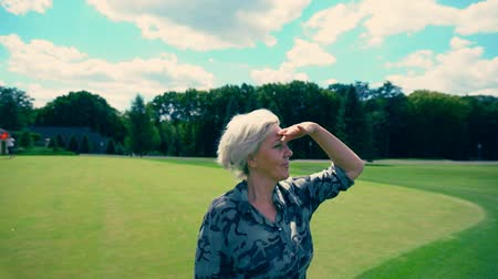 engrossed : Woman shading eyes while she looks out over lawn