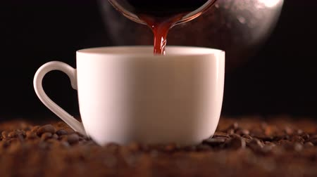 csészealj : Coffee pouring into mug sitting on coffee beans
