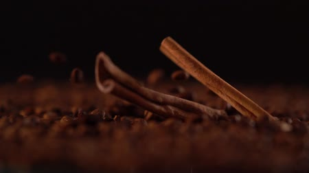 emtia : Sticks of cinnamon spice falling onto coffee