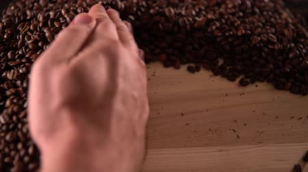 addiktív : Person swiping aside coffee beans with a hand Stock mozgókép
