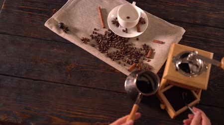 specialities : Person using spoon to scoop ground coffee into pot