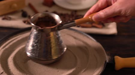 kitchenware : Person swirling a coffee pot on a plate of sand Stock Footage