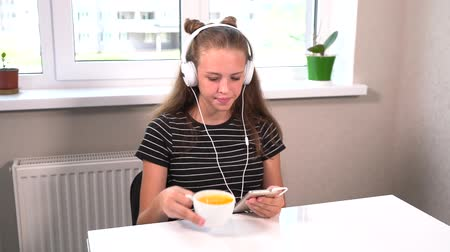 adolescents : Young girl sitting listening to music at home Stock Footage