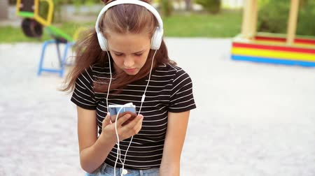 engrossed : Girl wearing headphones while holding phone