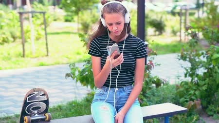 engrossed : Girl sitting on bench while listening to music