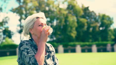 szomjúság : Blond woman outdoors in a park drinking Stock mozgókép