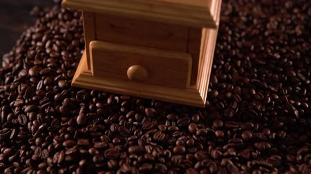 emtia : Wooden coffee mill on roasted coffee beans