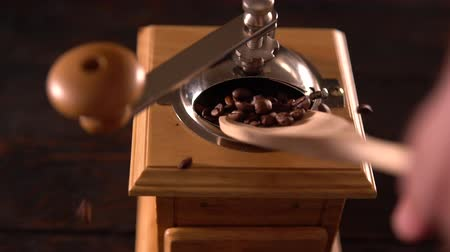 condimento : Person filling a wooden coffee grinder or mill