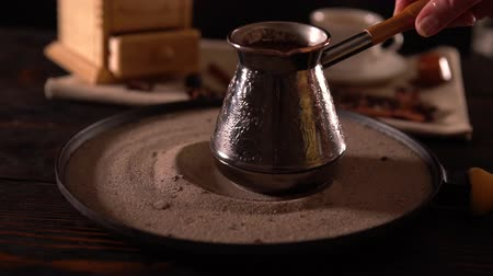 brew coffee : Person moving a coffee pot in circles on sand Stock Footage