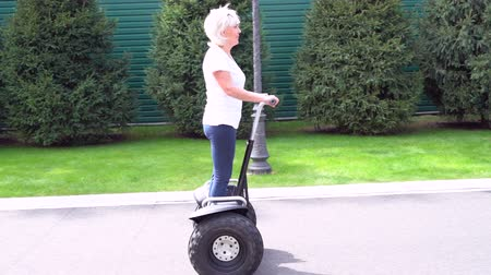 self balancing : Woman riding a Electric Personal Transporter along a street Stock Footage