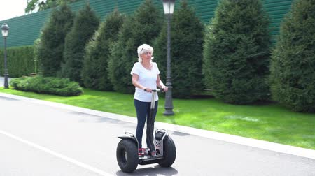 balanceamento : Woman riding past the camera on a Electric Personal Transporter Stock Footage