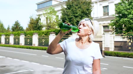 self balancing : Woman drinking from a bottle in the street