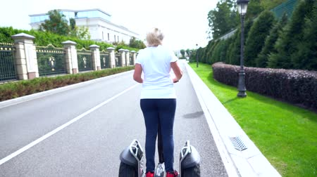 personal transporter : Woman riding away from the camera on a Electric Personal Transporter