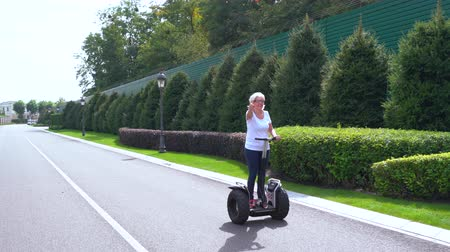 self balancing : Woman riding on a Electric Personal Transporter on a quiet street
