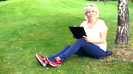 engrossed : Woman sketching on a clip board in a park Stock Footage