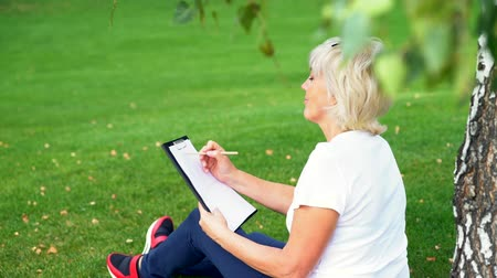 engrossed : Woman relaxing in a park sketching Stock Footage