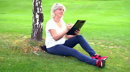 engrossed : Attractive mature woman sketching in a park