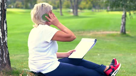 engrossed : Woman chatting on her mobile as she sits sketching