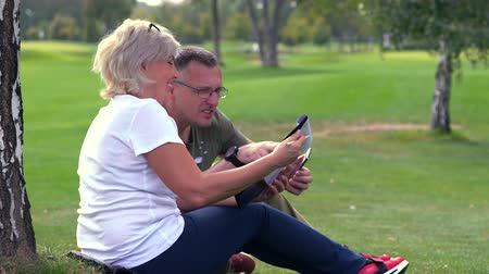 engrossed : Mature couple relaxing together in a park