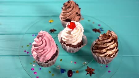 borrifar : Four freshly baked cupcakes with twirled icing Stock Footage
