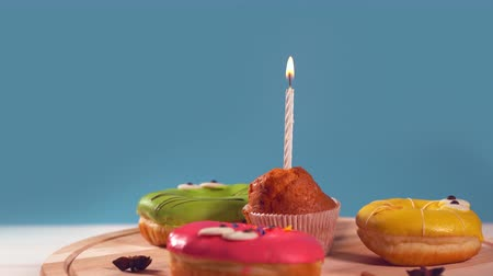 négy : Muffin with burning candle and iced donuts Stock mozgókép