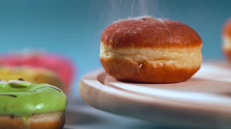 american cuisine : Rotating cream buns being sprinkled with sugar