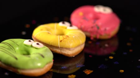 calorias : Three spinning colorful iced ring donuts Stock Footage