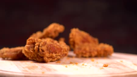 převrátit : Piece of crumbed fried chicken falling on a board