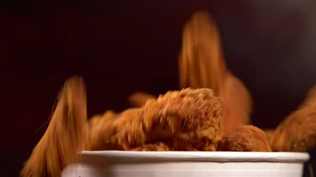 preparado : Pieces of crumbed fried chicken falling into a tub Stock Footage