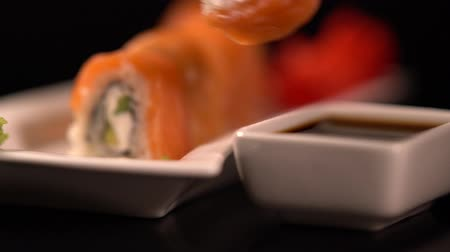 スターター : Sushi roll with chopsticks dipped in soya sauce