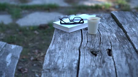 keménytáblás : Book, reading glasses and takeaway coffee