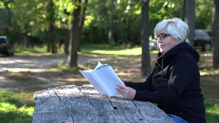 roman : Attractive older woman reading a book in a park