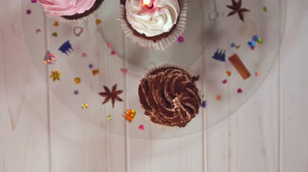 anason : Four iced cupcakes on a decorated glass plate Stok Video