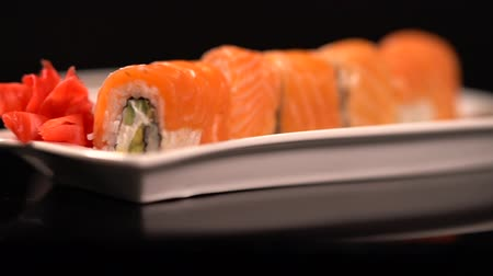 スターター : Plate of fresh salmon sushi rolls with soy sauce