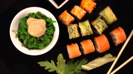 pauzinhos : Rotating view of sushi, seaweed salad and soy Stock Footage