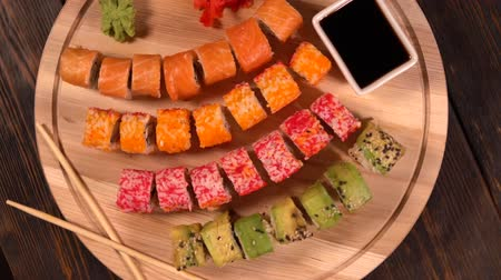 стартер : Rotating view of assorted sushi on a wooden board