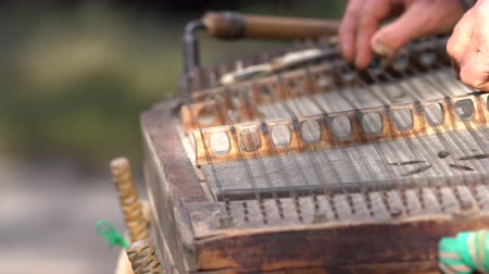 hammered : Man using hammered mallets to play a zither