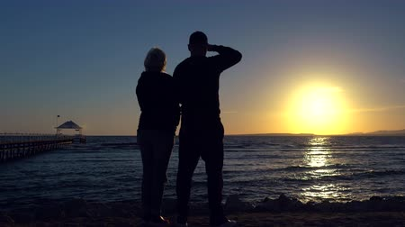 旅行の目的地 : Romantic couple standing watching an ocean sunset