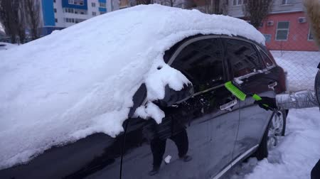 покрытый : Woman cleaning the car with snow brush Стоковые видеозаписи
