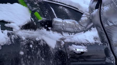 pristine : Brushing off the snow from car side windows