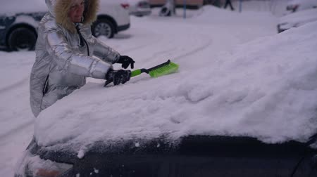 покрытый : Woman cleaning the car of snow, from low angle
