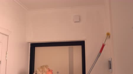 dungarees : Blond woman using a long roller to paint her house Stock Footage
