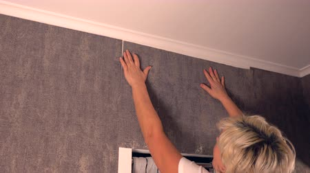 decorador : Woman hanging a sheet of wallpaper indoors