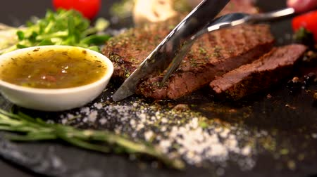 rump : Person slicing a tender portion of grilled steak Stock Footage