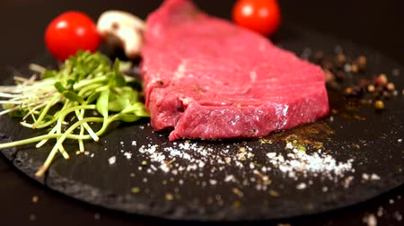 rump : Portion of raw beef tossed onto a black board