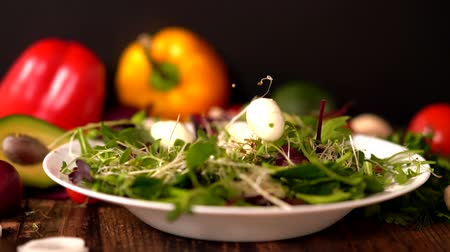 plated : Cooked shelled quail eggs falling on a salad Stock Footage