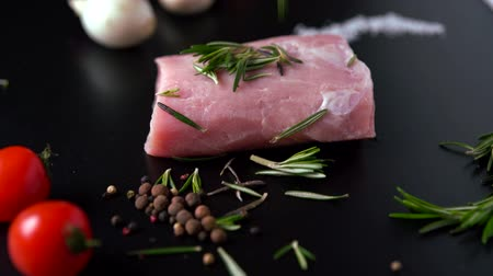pimenta em grão : Fresh rosemary being added to raw pork fillet