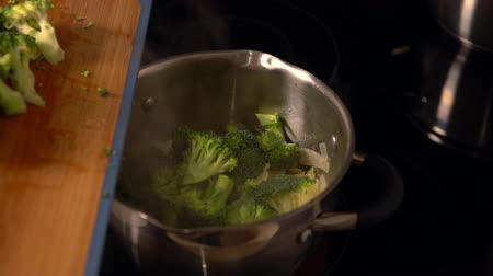 specialities : Cook adding fresh florets of broccoli
