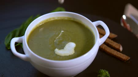 specialities : Chef garnishing broccoli soup with cream Stock Footage