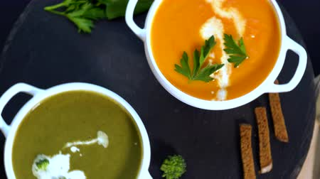 garnished : Bowls of broccoli and pumpkin soup
